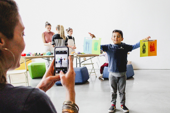 A young boy holds up artwork he has created while an adult takes a photo of him with her smartphone.