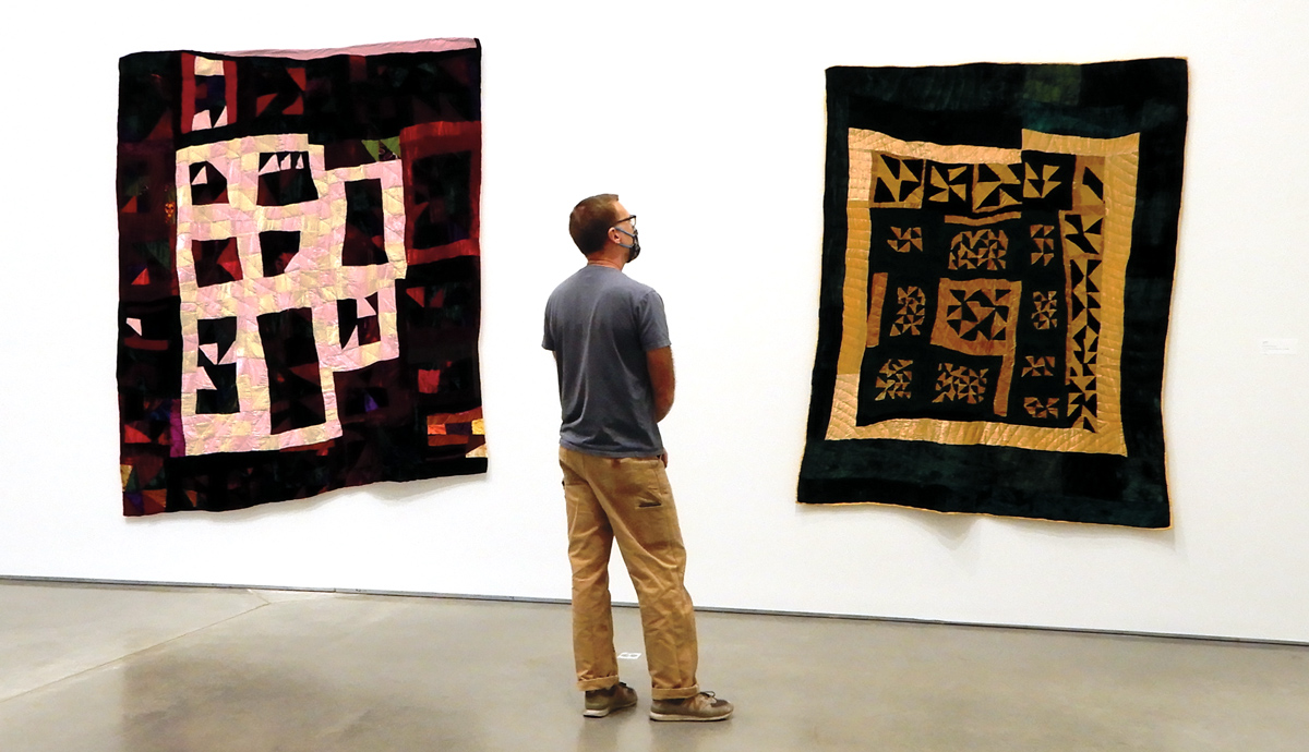 A man looks at two quilts by Rosie Lee Tompkins hung on a white wall in a gallery.