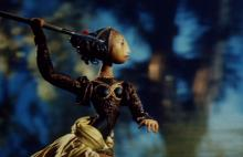 Film still: Puppet of a female figure appearing to prepare to throw a javelin.