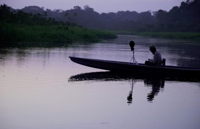 Film still: A canoe-like boat with a lone passenger floats on a river or lake during twilight. A boom micorphone is visible stading in the center of the boat.