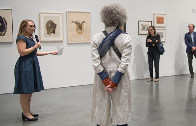 Curator Apsara DiQuinzio holds a microphone while addressing a tour group within a gallery at BAMPFA.